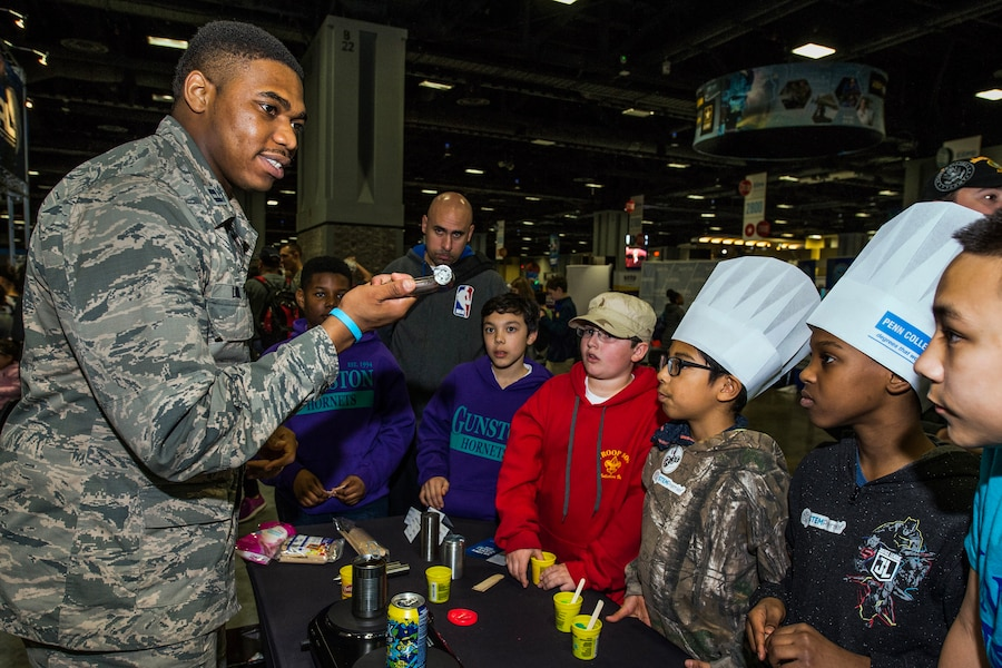 An airman standing at a table holds up a piece of a metal while talking to students gathered around.