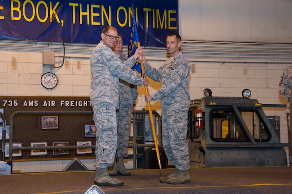 U.S. Air Force Col. Kenneth Lute, 624th Regional Support Group commander, gives Maj. Kenneth Ruggles Jr. command of the 48th Aerial Port Squadron during an assumption of command ceremony at Joint Base Pearl Harbor-Hickam, Hawaii, April 7, 2018.