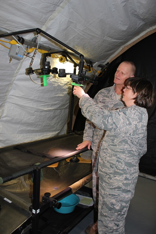 Lt. Col. Brandi Ritter and Lt. Col. Lewis Wilber, the Chief and Deputy Chief, Air Force Medical Evaluation Support Activity, examine the lights above a surgical table at the AMESA test facility at Ft. Detrick, Md. on Feb. 15, 2018. AFMESA investigated whether new, light-emitting diode (LED) lights could replace traditional surgical lights for use in deployed environments, but found that under the LEDs, surgeons could not determine if a patient's flesh was necrotic. (U.S. Air Force photo by Shireen Bedi)