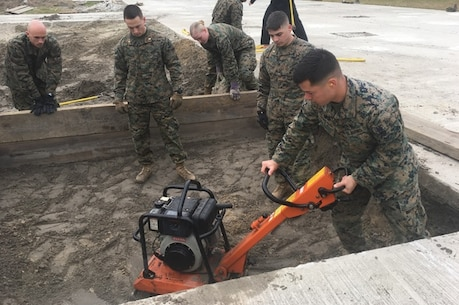 On March 19, 2018 Second Lieutenant Juan Gonzales, a Marine attending Combat Engineer Officer course 2-18 (CEO 2-18) at Marine Corps Engineer School aboard Camp Lejeune, N.C.; operates a compactor over an expedient crater repair. Pictured from left to right: Second Lieutenants Jon Roberts, Trevor Kenahan, Bethany Koshak, Thomas Raymond, and Juan Gonzales.