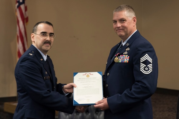 Lt. Col Micheal D. Howard, 188th Civil Engineering Commander, presents Cheif Master Sgt. Ronald W. Redding,188th Civil Engineering Squadron Emergency Management Chief, with the Meritorious Service Medal during Cheif Redding's retirement ceremony at Fort Smith, AR., Apr. 07, 2018. (U.S. Air National Guard photo by Tech. Sgt. Daniel Condit)