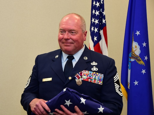 Chief Master Sgt. Robert Ussery of the 118th Wing holds an American flag at his retirement ceremony on April 8, 2018 at Berry Field Air National Guard Base, Nashville, Tennessee.