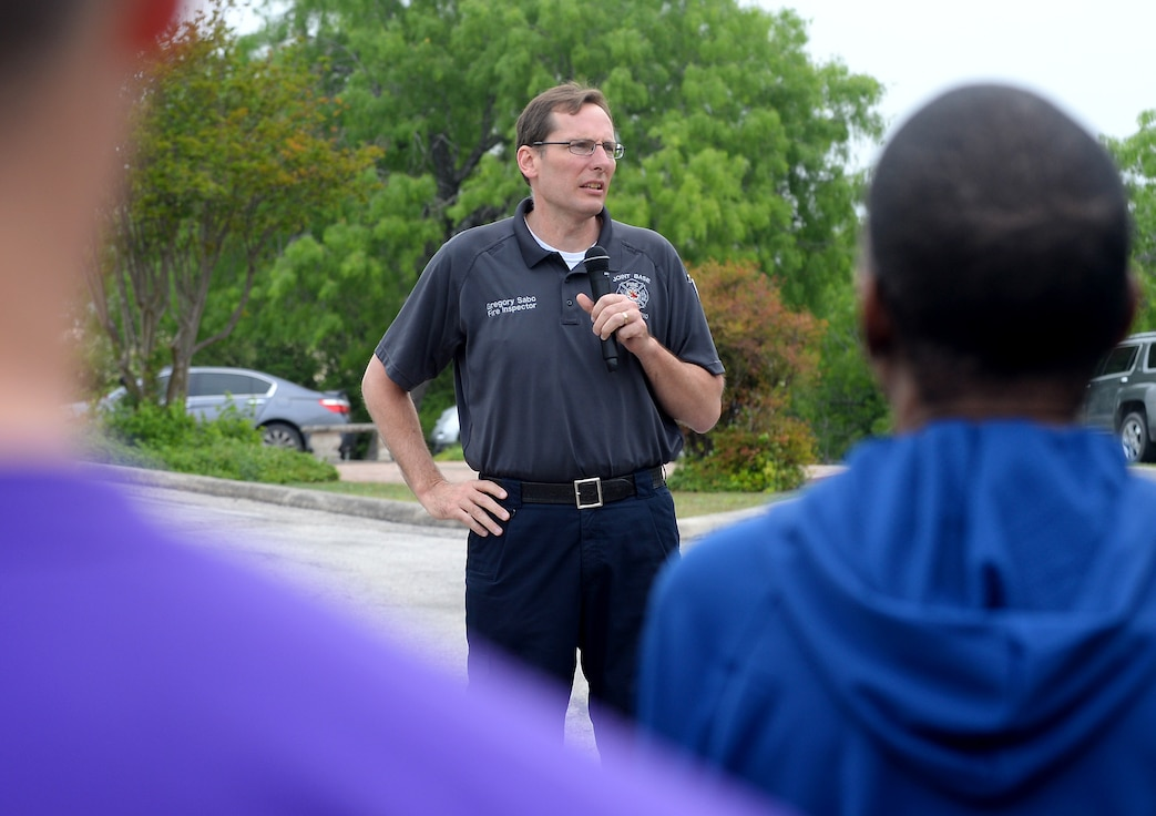 "Gregory Sabo, 502nd Civil Engineer Squadron fire inspector, discusses fire extinguisher use during the 67th Cyberspace Wing annual safety day event at Joint Base San Antonio-Lackland, Texas, April 6, 2018. The sports and recreation themed event included several sports competitions and a ""Gunslinger"" warrior challenge to provide the participants more situational awareness and risk management techniques to consider during these activities. (U.S. Air Force photo by Tech. Sgt. R.J. Biermann)"