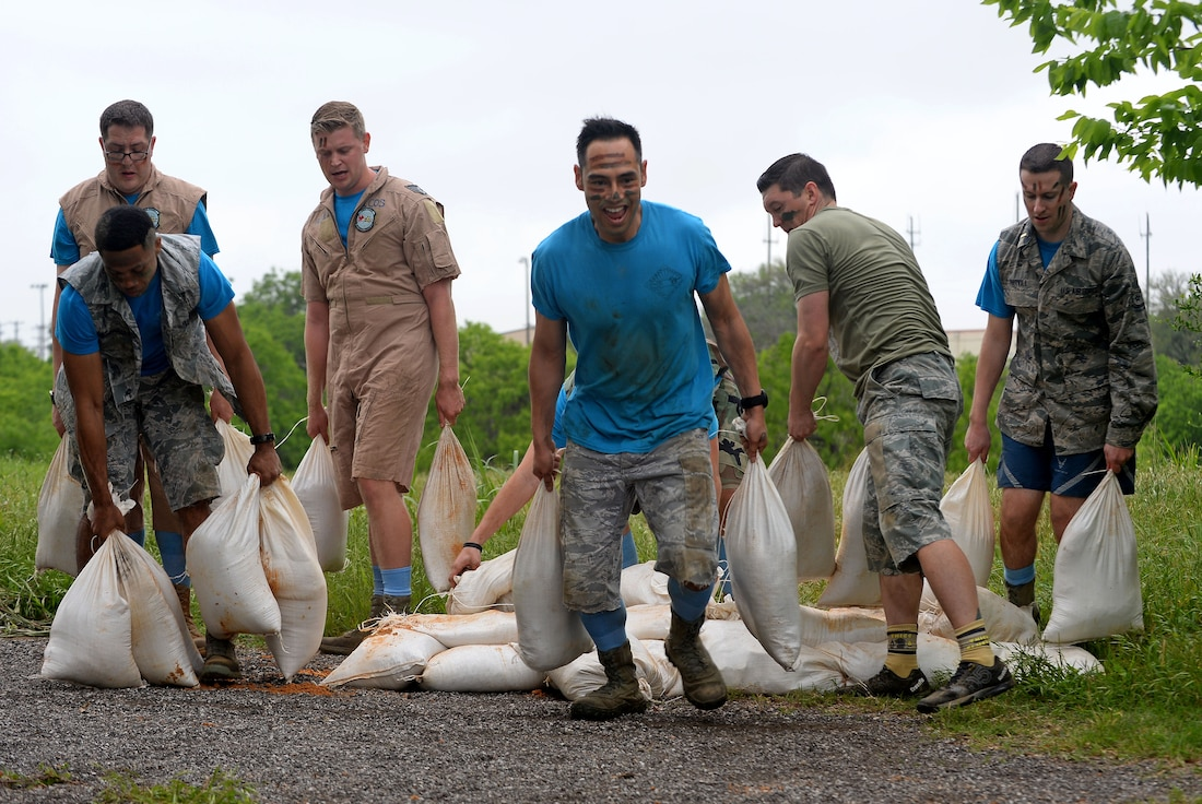 "The 91st Cyberspace Operations Squadron ""Demon Chasers"" team builds a sandbag wall during the 67th Cyberspace Wing annual safety day ""Gunslinger"" warrior challenge at Joint Base San Antonio-Lackland, Texas, April 6, 2018. The challenge pitted several teams against one another in seven timed events, where the 68th Network Warfare Squadron ""Purple Dragons"" captured first place. (U.S. Air Force photo by Tech. Sgt. R.J. Biermann)"