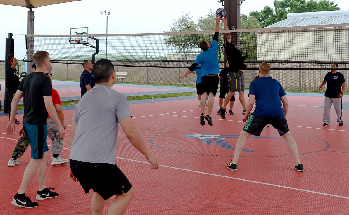 "Senior NCOs and officers, from the 67th Cyberspace Wing, compete in a volleyball tournament during the annual safety day event at Joint Base San Antonio-Lackland, Texas, April 6, 2018. The sports and recreation themed event included several sports competitions and a ""Gunslinger"" warrior challenge to provide the participants more situational awareness and risk management techniques to consider during these activities. (U.S. Air Force photo by Tech. Sgt. R.J. Biermann)"