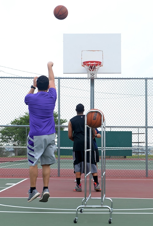 """A 67th Cyberspace Wing Airman shoots a 3-pointer in a 3-point tournament during the annual safety day event at Joint Base San Antonio-Lackland, Texas, April 6, 2018. The sports and recreation themed event included several sports competitions and a """"Gunslinger"""" warrior challenge to provide the participants more situational awareness and risk management techniques to consider during these activities. (U.S. Air Force photo by Tech. Sgt. R.J. Biermann)"""
