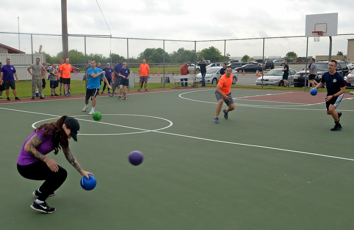"Airmen and junior NCOs from the 67th Cyberspace Wing compete in a dodgeball game during the annual safety day event at Joint Base San Antonio-Lackland, Texas, April 6, 2018. The sports and recreation themed event included several sports competitions and a ""Gunslinger"" warrior challenge to provide the participants more situational awareness and risk management techniques to consider during these activities. (U.S. Air Force photo by Tech. Sgt. R.J. Biermann)"