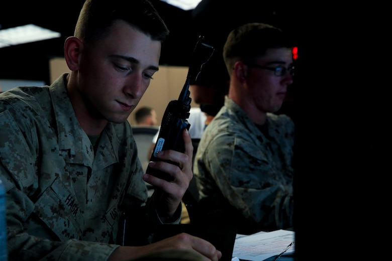Pfc. Gage Haga, transmissions system operator, 1st Battalion, 4th Marine Regiment, stationed out of  Marine Corps Base Camp Pendleton, Calif., communicates with units acting as simulated casualties during Command Post Exercise 2 at the Battle Simulation Center aboard the Marine Corps Air Ground Combat Center, Twentynine Palms, Calif., March 29, 2018. CPX-2 is a  two-part training event that focuses on training battalion staff and is a part of TALONEX 2-18, a pre-deployment training event that coincides with Weapons and Tactics Instructors Course.  (U.S. Marine Corps photo by Lance Cpl. Isaac Cantrell)