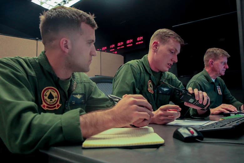 Capt. Theodore Linn (right), AH-1 pilot, Marine Light Attack Helicopter Squadron 267, and 1st Lt. Andrew Donohue (left), AH-1 pilot, HMLA-267, record the time during Command Post Exercise 2 at the Battle Simulation Center aboard the Marine Corps Air Ground Combat Center, Twentynine Palms, Calif., March 29, 2018. CPX-2 is a two-part training event that focuses on training battalion staff and is a part of TALONEX 2-18, a pre-deployment training event that coincides with Weapons and Tactics Instructors Course. (U.S. Marine Corps photo by Lance Cpl. Isaac Cantrell)