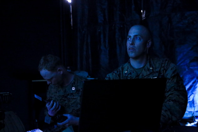 Maj. Jesse Attig (right), modeling and simulations officer, Marine Air Ground Task Force Training Command, evaluates units during Command Post Exercise 2 at the Battle Simulation Center aboard the Marine Corps Air Ground Combat Center, Twentynine Palms, Calif., March 29, 2018. CPX-2 is a two-part training event that focuses on training battalion staff and is a part of TALONEX 2-18, a pre-deployment training event that coincides with Weapons and Tactics Instructors Course. (U.S. Marine Corps photo by Lance Cpl. Isaac Cantrell)