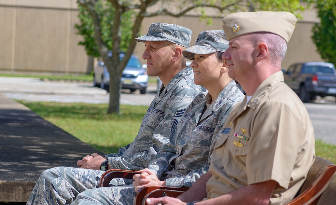 """U.S. Air Force Chief Master Sgt. Ken Carter (left) and Col. Debra Lovette (center) attend the Center for Naval Aviation Technical Training Unit Keesler's Chief Petty Officer Birthday Ceremony at Keesler Air Force Base, Mississippi, April 5, 2018. The U.S. Navy's Chief Petty Officers are celebrating 125 years of heritage and the naval tradition of Unity, Service and Navigation, which is part of their rate emblem, is symbolized by a fouled anchor with the letters """"USN"""" centered on the anchor. (U.S. Air Force photo by André Askew)"""