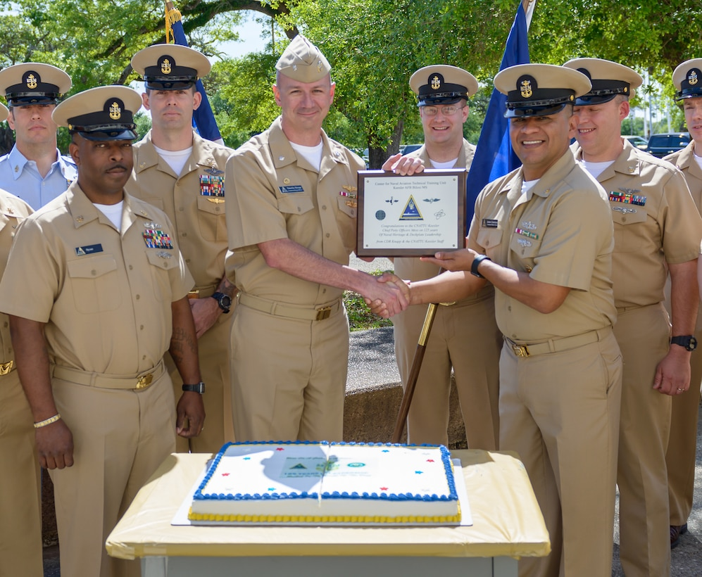 """U.S. Navy Cmdr. Timothy Knapp, Center for Naval Aviation Technical Training Unit Keesler commanding officer, presents the Chief's Mess with a plaque during the CNATTU Keesler's Chief Petty Officer Birthday Ceremony at Keesler Air Force Base, Mississippi, April 5, 2018. The U.S. Navy's Chief Petty Officers are celebrating 125 years of heritage and the naval tradition of Unity, Service and Navigation, which is part of their rate emblem, is symbolized by a fouled anchor with the letters """"USN"""" centered on the anchor. (U.S. Air Force photo by André Askew)"""