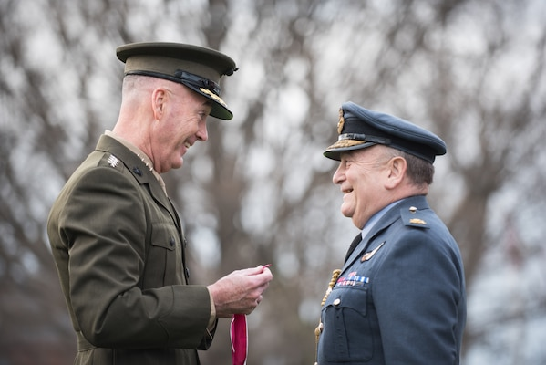 U.S. Marine Corps Gen. Joseph F. Dunford, Jr., chairman of the Joint Chiefs of Staff, prepares to award Air Chief Marshal Sir Stuart Peach, United Kingdom Chief of Defense, the Legion of Merit during an Armed Forces Full Honor Arrival Ceremony at Joint Base Myer-Henderson Hall, April 6, 2018. The award was presented for his efforts to bolster key military support for the Defeat-ISIS Coalition contributing to the significant degradation of ISIS in Iraq and Syria. This is Air Chief Marshal Peach's last visit before he transitions into a new role as the Chairman of the NATO Military Committee. (DoD Photo by U.S. Army Sgt. James K. McCann)