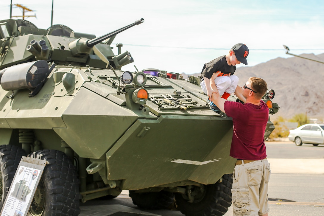 Sgt. Nathan J. Wepking, company master gunner, 3rd Light Armored Reconnaissance Battalion, lifts his son, Joshua Parker Wepking, off of a light armored vehicle during the 18th Annual Car Show and Street Fair, which was hosted by the Twentynine Palms Chamber of Commerce in Twentynine Palms, Calif., March 31, 2018.  The annual event is used to bring the community of Twentynine Palms and the Marine Corps Air Ground Combat Center, located in Twentynine Palms, together as well as support local businesses. (U.S. Marine Corps photo by Lance Cpl. Rachel K. Porter)