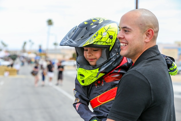 Gunnery Sgt. Joel A. Nieves, data chief, Tactical Training Exercise Control Group, holds his son, Nathaniel Nieves, 5, after his participation in the soapbox derby during the 18th Annual Car Show and Street Fair, which was hosted by the Twentynine Palms Chamber of Commerce in Twentynine Palms, Calif., March 31, 2018. The annual event is used to bring the community of Twentynine Palms and the Marine Corps Air Ground Combat Center, located in Twentynine Palms, together as well as support local businesses. (U.S. Marine Corps photo by Lance Cpl. Rachel K. Porter)