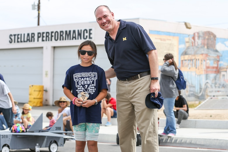 Cmrd. David Stroud, chaplin, Combat Center Protestant Chapel, awards Maribella Grotberg, 10, for winning the General's Choice Soapbox Derby during the 18th Annual Car Show and Street Fair, which was hosted by the Twentynine Palms Chamber of Commerce in Twentynine Palms, Calif., March 31, 2018. The annual event is used to bring the community of Twentynine Palms and the Marine Corps Air Ground Combat Center, located in Twentynine Palms, together as well as support local businesses. (U.S. Marine Corps photo by Lance Cpl. Rachel K. Porter)