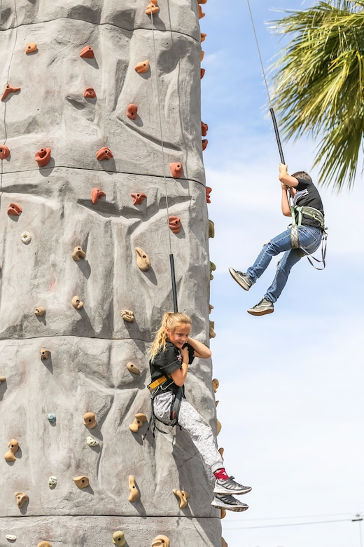 Kylie Hluk, 9, granddaughter of Jeff Hluk, Twentynine Palms patron, and Daniel Garcia, 8, nephew of Ramiro Garcia, Twentynine Palms patron, rappel from the Hand To Hand Marital Arts rock climbing tower during the 18th Annual Car Show and Street Fair, which was hosted by the Twentynine Palms Chamber of Commerce in Twentynine Palms, Calif., March 31, 2018. The annual event is used to bring the community of Twentynine Palms and the Marine Corps Air Ground Combat Center, located in Twentynine Palms, together as well as support local businesses. (U.S. Marine Corps photo by Lance Cpl. Rachel K. Porter)