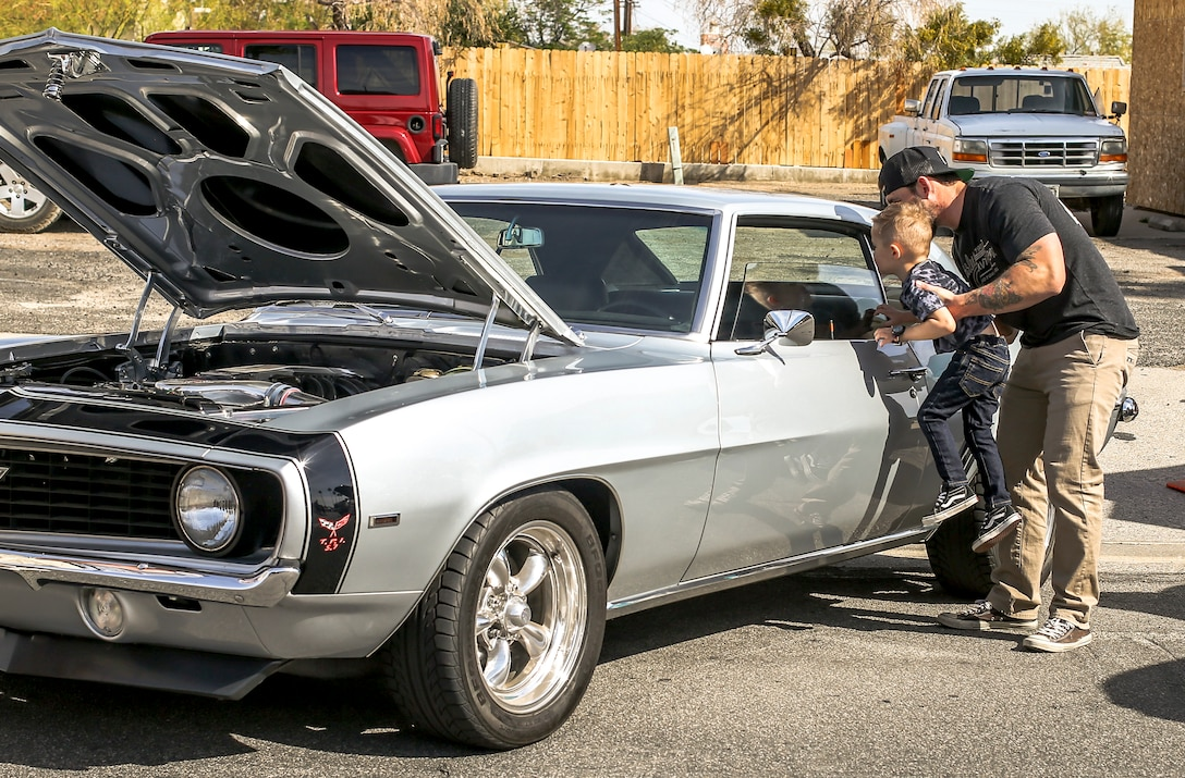 Robert McCabe, government contractor, Advancia Technology, shows his son the interior of a vehicle during the 18th Annual Car Show and Street Fair, which was hosted by the Twentynine Palms Chamber of Commerce in Twentynine Palms, Calif., March 31, 2018. The annual event is used to bring the community of Twentynine Palms and the Marine Corps Air Ground Combat Center, located in Twentynine Palms, together as well as support local businesses. (U.S. Marine Corps photo by Lance Cpl. Rachel K. Porter)