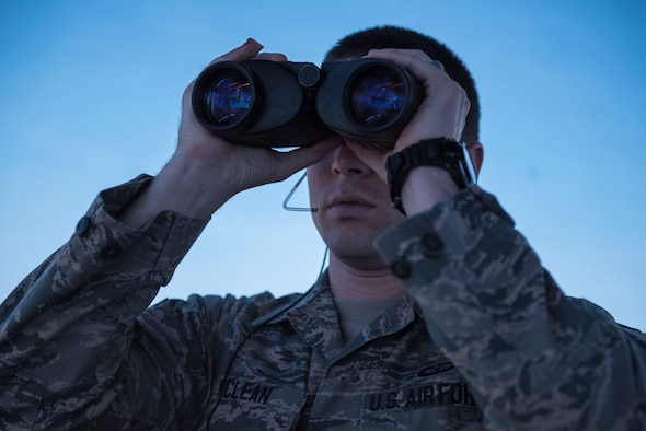 U.S. Air Force Senior Airman Samuel McLean, 20th Operations Support Squadron air traffic controller, looks for aircraft through binoculars at Shaw Air Force Base, S.C., April 5, 2018.