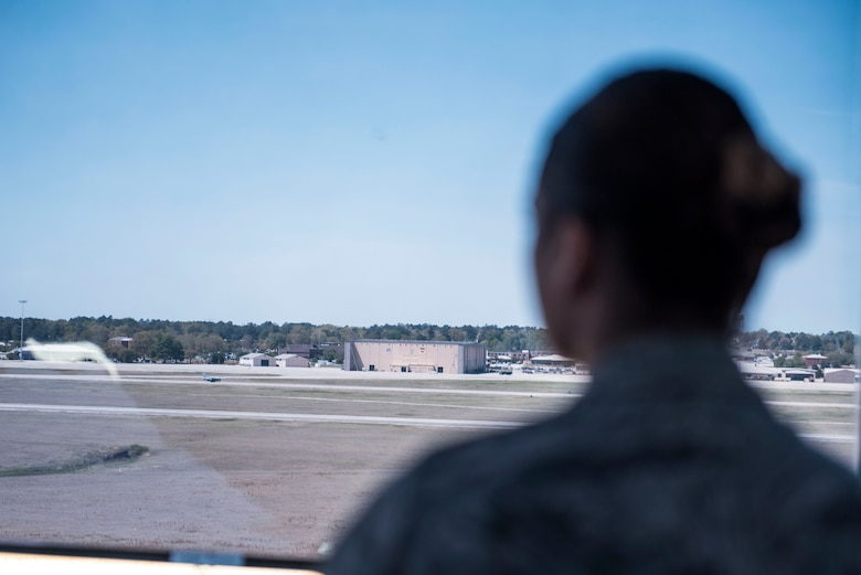 A U.S. Airman assigned to the 20th Operations Support Squadron air traffic control tower watches an F-16CM Fighting Falcon taxi down the runway at Shaw Air Force Base, S.C., April 5, 2018.