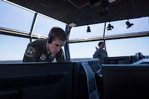 U.S. Air Force Capt. Kyle Rasmussen, 55th Fighter Squadron pilot acting as the air traffic control tower flying supervisor, records information on a computer while Staff Sgt. Elizabeth Gordon, 20th Operations Support Squadron watch supervisor, speaks with tower Airmen at Shaw Air Force Base, S.C., April 5, 2018.