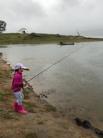 A little girl waits for the fish to bite during Kids Fishing Day on April 7, 2018 at Eastman Lake. More than 30 children and their families participated in this years event despite wet, rainy weather.