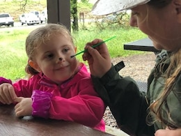 A girl gets her face painted April 7, 2018 during Kids Fishing Day at Eastman Lake. In addition to fishing, there were plenty of activities such as raffles, a casting contest and a DJ playing music for dancing.