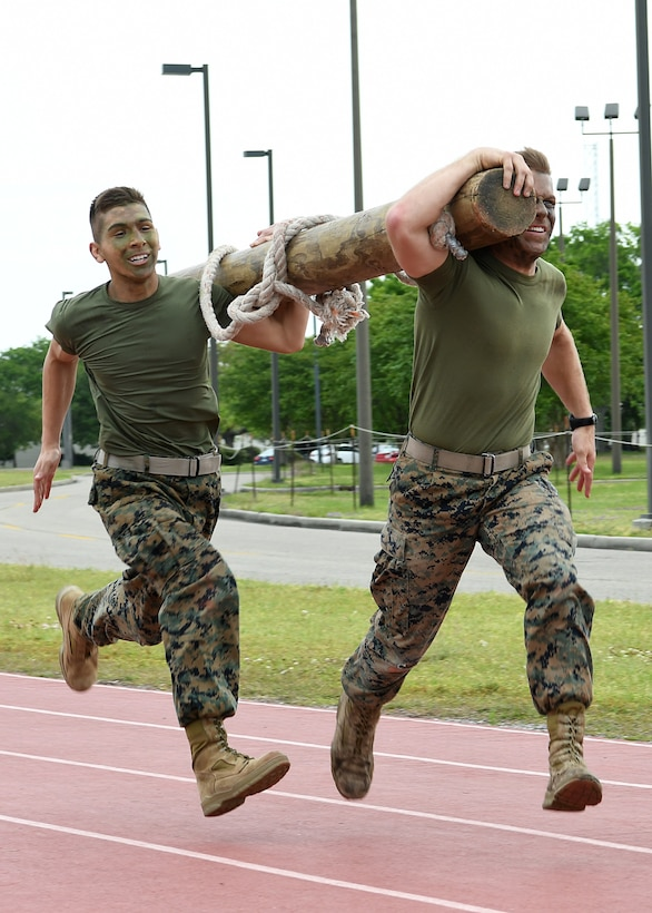 U.S. Marine Corps Private First Class Anthony Maccarelli, Keesler Marine Detachment meteorological oceanographic analyst forecaster student, and Lance Corporal Andrew Parker, Keesler Marine Detachment MOAF student, participate in the log race during the 2nd Annual Warrior Day at the Triangle Track at Keesler Air Force Base, Mississippi, April 6, 2018. The event served to promote unit cohesion, camaraderie and small unit leadership. The winning team received a Warrior Medallion as well as a coin. (U.S. Air Force photo by Airman 1st Class Suzie Plotnikov)