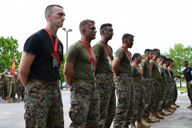 Keesler Marine Detachment students receive their first place warrior medallions during the 2nd Annual Warrior Day at the Keesler Marine Detachment at Keesler Air Force Base, Mississippi, April 6, 2018. Ten teams competed against each other in eight events that served to promote unit cohesion, camaraderie and small unit leadership. The winning team received a Warrior Medallion as well as a coin. (U.S. Air Force photo by Airman 1st Class Suzie Plotnikov)