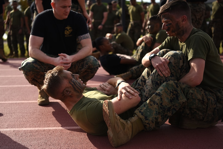 Keesler Marine Detachment students do crunches for the hip race at the Triangle Track during the 2nd Annual Warrior Day at Keesler Air Force Base, Mississippi, April 6, 2018. The hip race included 50 ammo can lifts, 20 burpees, 50 squats, 50 crunches and five squad pushups. The event served to promote unit cohesion, camaraderie and small unit leadership. (U.S. Air Force photo by Airman 1st Class Suzie Plotnikov)