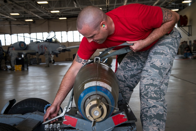 Staff Sgt. Kyle Palmer 75th Aircraft Maintenance Unit weapons load crewmember secures an inert munition on an A-10C Thunderbolt II during a weapons load competition, April 9, 2018, at Moody Air Force Base, Ga. The 75th and 74th AMUs went head to head with each crew competing to load three munitions onto an A-10 quicker and with less discrepancies than the other. Crews were also judged on dress and appearance and a written test based on munitions knowledge. (U.S. Air Force photo by Senior Airman Janiqua P. Robinson)
