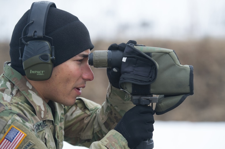 Army Spc. Arturo Dominguez, a native of Okeechobee, Fla., assigned to Charlie Troop, 1st Squadron, 40th Cavalry Regiment (Airborne), 4th Infantry Brigade Combat Team (Airborne), 25th Infantry Division, U.S. Army Alaska, uses a spotting scope to observe a fellow soldier's accuracy with a M2010 Enhanced Sniper Rifle on Statler range at Joint Base Elmendorf-Richardson, Alaska, April 6, 2018, during marksmanship training.  A sniper's main responsibility is to deliver discriminatory, highly accurate rifle fire against enemy targets that cannot be engaged successfully by the regular rifleman due to range, size, location, fleeting nature, or visibility.