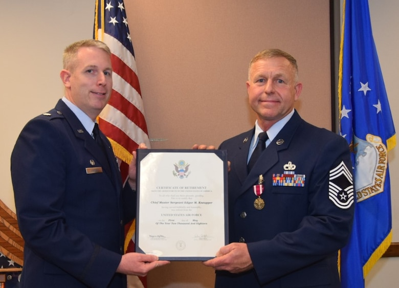 Lt. Col. Travis Hartley, 74th Aerial Port Squadron commander, presents a retirement certificate to Chief Master Sgt. Edgar M. Kneupper, 74th APS operations superintendent, April, 7 2018 on Joint Base San Antonio-Lackland, Texas. Kneupper initially enlisted in the Navy in 1985 before transitioning to the Air Force in 1995. (U.S. Air Force photo by Tech Sgt. Carlos J. Treviño)