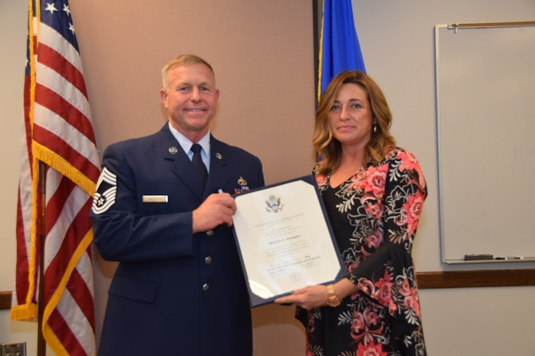 Chief Master Sgt. Edgar M. Kneupper, 74th Aerial Port Squadron operations superintendent, presented a certificate of appreciation to his wife, Michelle,  April, 7 2018 at his retirement ceremony on Joint Base San Antonio-Lackland, Texas.  In his civilian life, Kneupper is a fire fighter for the City of Austin, Texas.
