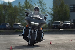 A motorcyclist drives between cones during a pre-ride skills assessment at Joint Base Elmendorf-Richardson, Alaska. At JBER, the riding season typically runs from May to October and motorcycle operations are only allowed when road conditions are green.