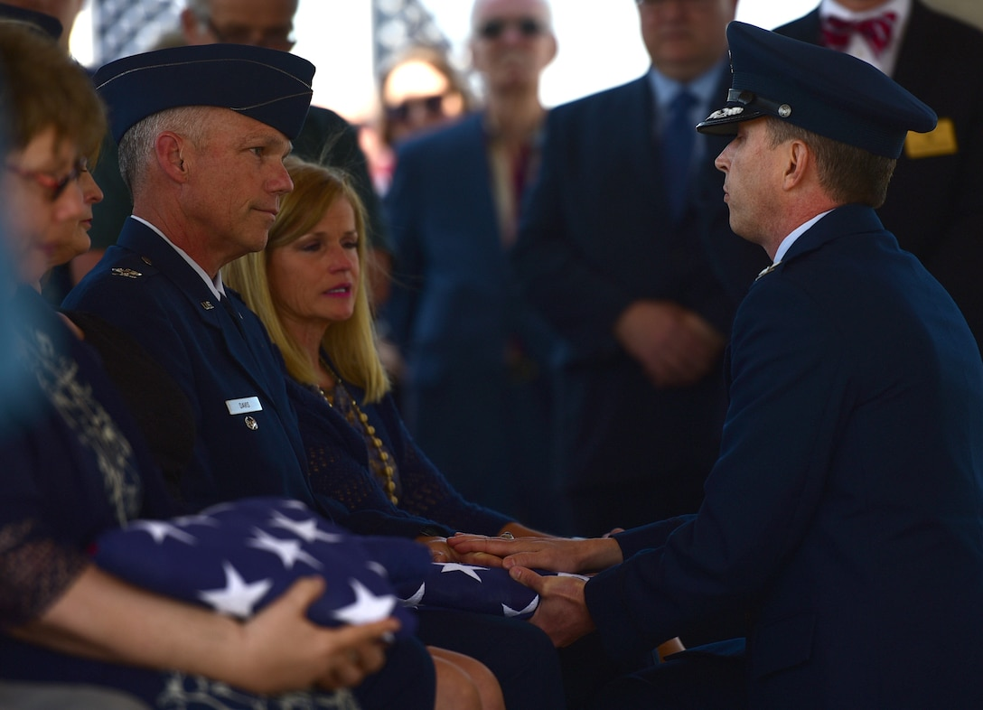 A Seymour Johnson Air Force Base Honor Guardsman presents a flag in honor of Col. Edgar Davis to his son Col. Alan Davis during his funeral ceremony April 6, 2018, Goldsboro, North Carolina. After being shot down over Laos during the Vietnam War in 1968, a Laotian villager buried the remains. In 2015, the villager's son reached out regarding the location of the remains. The Defense POW/MIA Accounting Agency recovered Davis' remains in 2017. (U.S. Air Force photo by Senior Airman Christian Clausen)