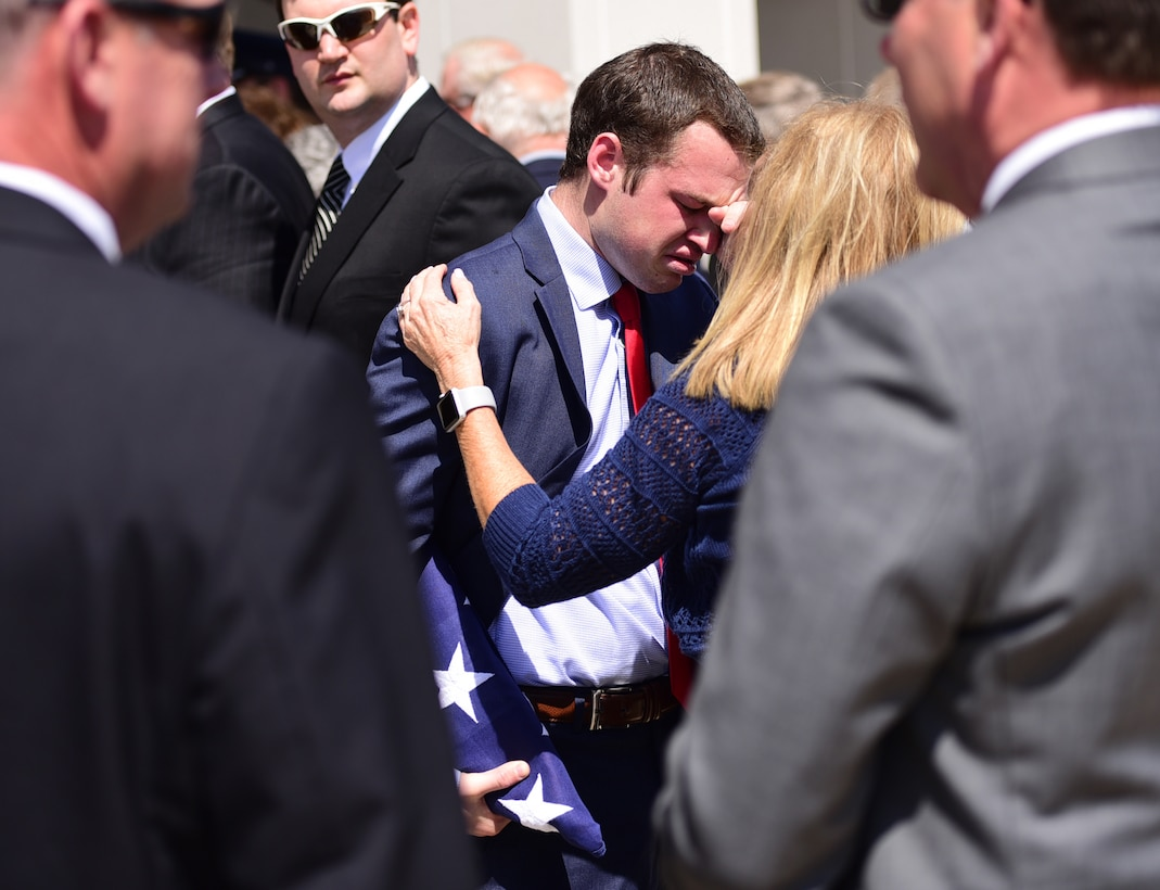 Matt Davis, grandson of Col. Edgar Davis embraces a family member after his grandfather's funeral ceremony April 6, 2018, Goldsboro, North Carolina. After being shot down over Laos during the Vietnam War in 1968, a Laotian villager buried the remains. In 2015, the villager's son reached out regarding the location of the remains. The Defense POW/MIA Accounting Agency recovered Davis' remains in 2017. (U.S. Air Force photo by Senior Airman Christian Clausen)
