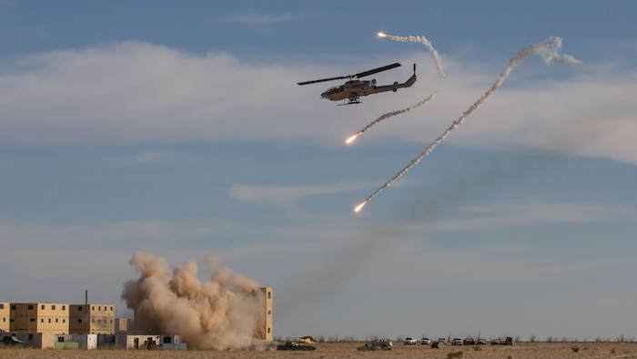 A U.S. Marine Corps AH-1W Super Cobra with Marine Aviation Weapons and Tactics Squadron 1 launches rockets at simulated enemy targets and deploys flares during a tactical demonstration in support of Weapons and Tactics Instructor course 2-18 at Yodaville, Yuma, Ariz., April 4.