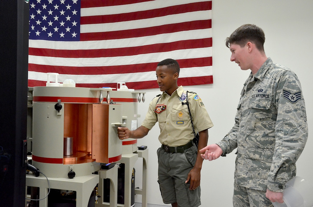 Larry Edgecombe, an 8th grader at Holy Trinity Episcopal Academy and member of Boy Scout Troop #355, opens the door of a gamma ray detector as Staff Sgt. Nicholas Jarvis, a radiochemistry lab technician, observes and explains how the detector works.  Edgecombe was one of 98 scouts who visited the Air Force Technical Applications Center March 31, 2018 to earn the Nuclear Science Merit Badge with the help of AFTAC Airmen.  (U.S. Air Force photo by Susan A. Romano)