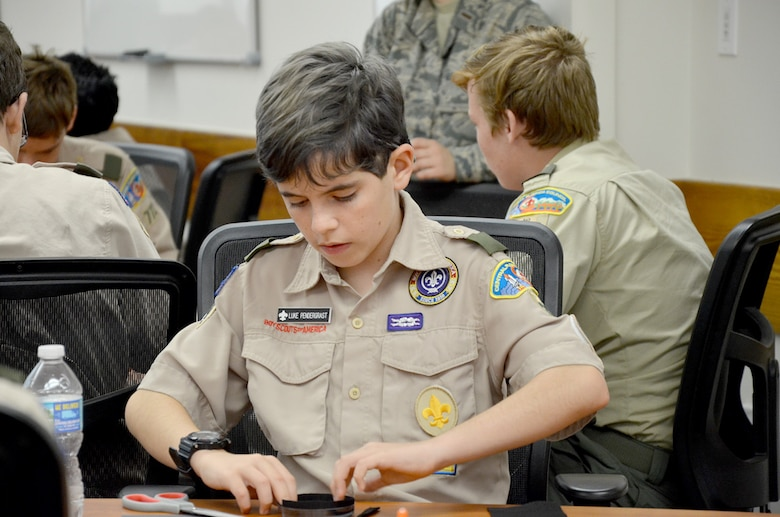 Luke Pendergrast, a Boy Scout from Troop 330 in Ormond Beach, Fla., carefully molds black felt in a petri dish to create a cloud chamber to visualize condensation trails left by ionizing radiation.  Pendergrast attended the Nuclear Science Merit Badge event hosted by the Air Force Technical Applications Center, Patrick AFB, Fla,. March 31, 2018.  (U.S. Air Force photo by Susan A. Romano)