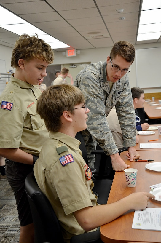 Capt. Jason Goins, a scientist with the Air Force Technical Applications Center, helps Boy Scouts Daniel Kirchhof, a 9th grader at University High School in Orlando, and Ethan Jesse, an 8th grader from Innovation Middle School in Orlando, during a Boy Scout Merit event hosted by the nuclear treaty monitoring center at Patrick AFB, Fla., March 31, 2018.  Goins was one of several Airmen from AFTAC who volunteered to help troops earn the badge.  (U.S. Air Force photo by Susan A. Romano)