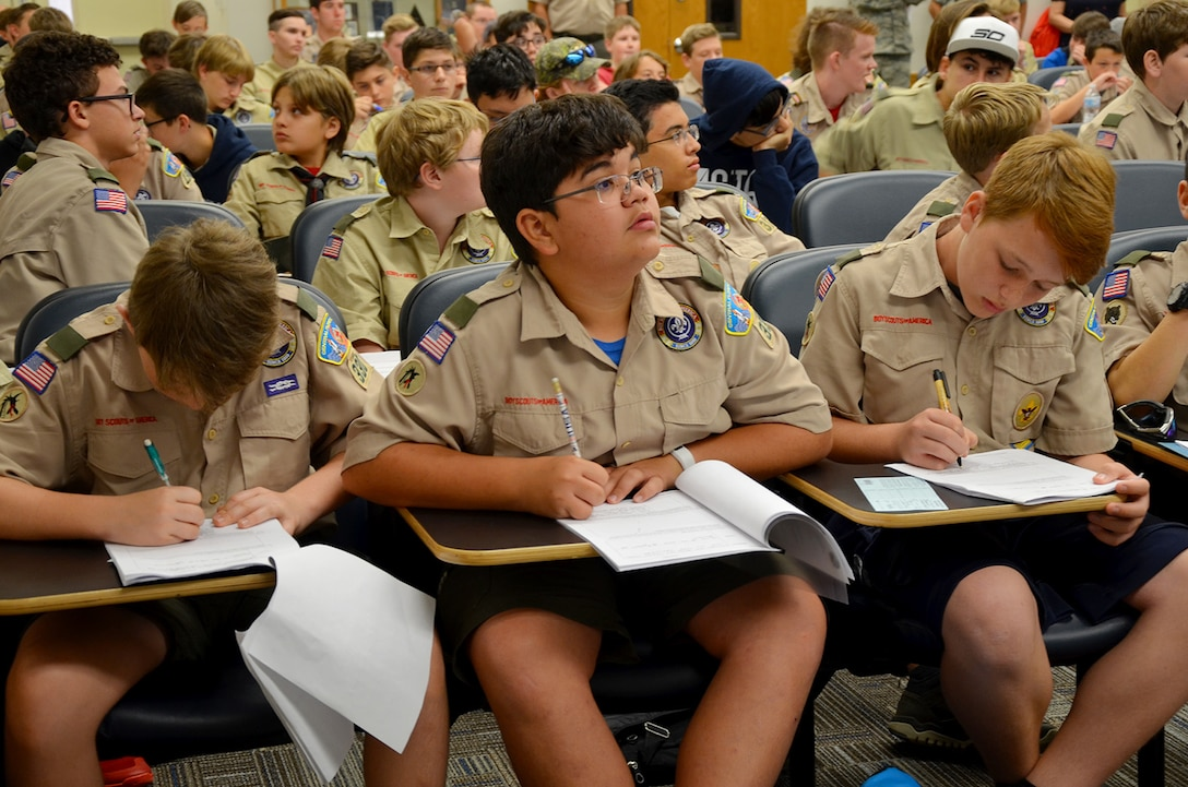 Jake Shipley (center), a 13-year-old Boy Scout from Hoover Middle School in Melbourne Beach, Fla., glances at PowerPoint slides as fellow scouts Ryan Herbruger (left) and Grand Newcombe (right) take notes during the Nuclear Science Merit Badge event hosted by the Air Force Technical Applications Center, Patrick AFB, Fla., March 31, 2018.  Shipley and his fellow scouts from Troop #330 earned the badge with the help of volunteers from the nuclear treaty monitoring center.  (U.S. Air Force photo by Susan A. Romano)