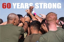 Marines with 3rd Marine Logistics Group huddle together to cheer on their flag football team during 3rd MLG's 60th Anniversary celebration April 10, 2018 on Camp Hansen, Okinawa, Japan. 3rd MLG Marines and Sailors conquered numerous challenges and competed in various team competitions such as sports, fire team and squad competitions, and tug-of-war, and took part in family events and a cake-cutting ceremony. The anniversary celebration built camaraderie between the service members and families. (U.S. Marine Corps photo by Pfc. Hannah Hall)