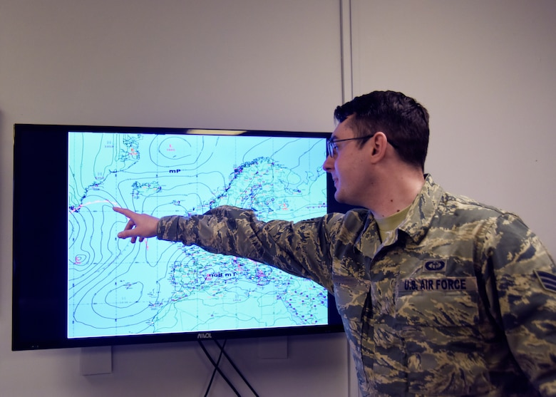 A 48th Operations Support Squadron weather forecaster journeyman displays a surface analysis map during the office morning weather briefing at Royal Air Force Lakenheath, England, March 20. Forecasters support aircrews by keeping them apprised of weather conditions, which allows them to focus on the Liberty Wing's mission to provide responsive combat airpower and support. (U.S. Air Force photo/Senior Airman Abby L. Finkel)