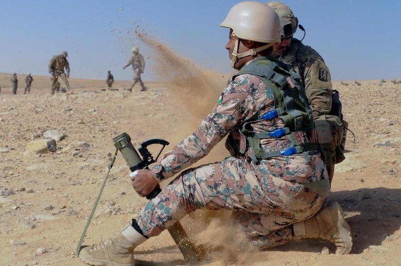U.S. Army Spc. Bradley Wilkerson, an indirect fire infantryman, 1st Battalion, 184th Infantry Regiment, oberves a Jordan Armed Forces 11th Border Security soldier during a 60 mm mortar live fire outside of Amman, Jordan, April 4, 2018.
