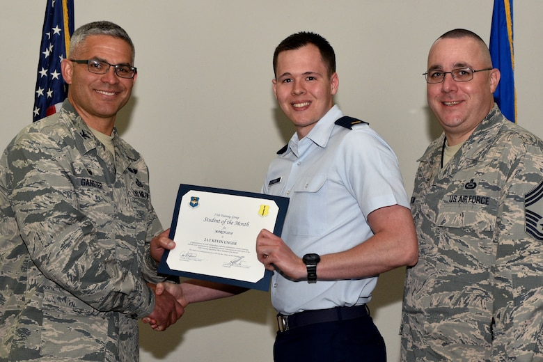 U.S. Air Force Col. Alex Ganster, 17th Training Group commander, and Chief Master Sgt. Daniel Stein, 17th TRG superintendent, present the 315th Training Squadron Officer Student of the Month certificate to 2nd Lt. Kevin Unger, 315th TRS trainee, in the Event Center on Goodfellow Air Force Base, Texas, April 6, 2018. The 315th TRS's vision is to develop combat-ready intelligence, surveillance and reconnaissance professionals and promote an innovative squadron culture and identity unmatched across the U.S. Air Force. (U.S. Air Force photo by Senior Airman Randall Moose/Released)