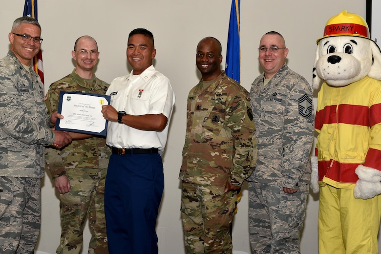 U.S. Air Force Col. Alex Ganster, 17th Training Group commander, and Chief Master Sgt. Daniel Stein, 17th TRG superintendent, present the 312th Training Squadron Student of the Month certificate to U.S. Army Private 1st Class John Nguyen-Vu, 312th TRS trainee, in the Event Center on Goodfellow Air Force Base, Texas, April 6, 2018.  The 312th TRS's mission is to provide Department of Defense and international customers with mission ready fire protection and special instruments graduates and provide mission support for the Air Force Technical Applications Center. (U.S. Air Force photo by Senior Airman Randall Moose/Released)