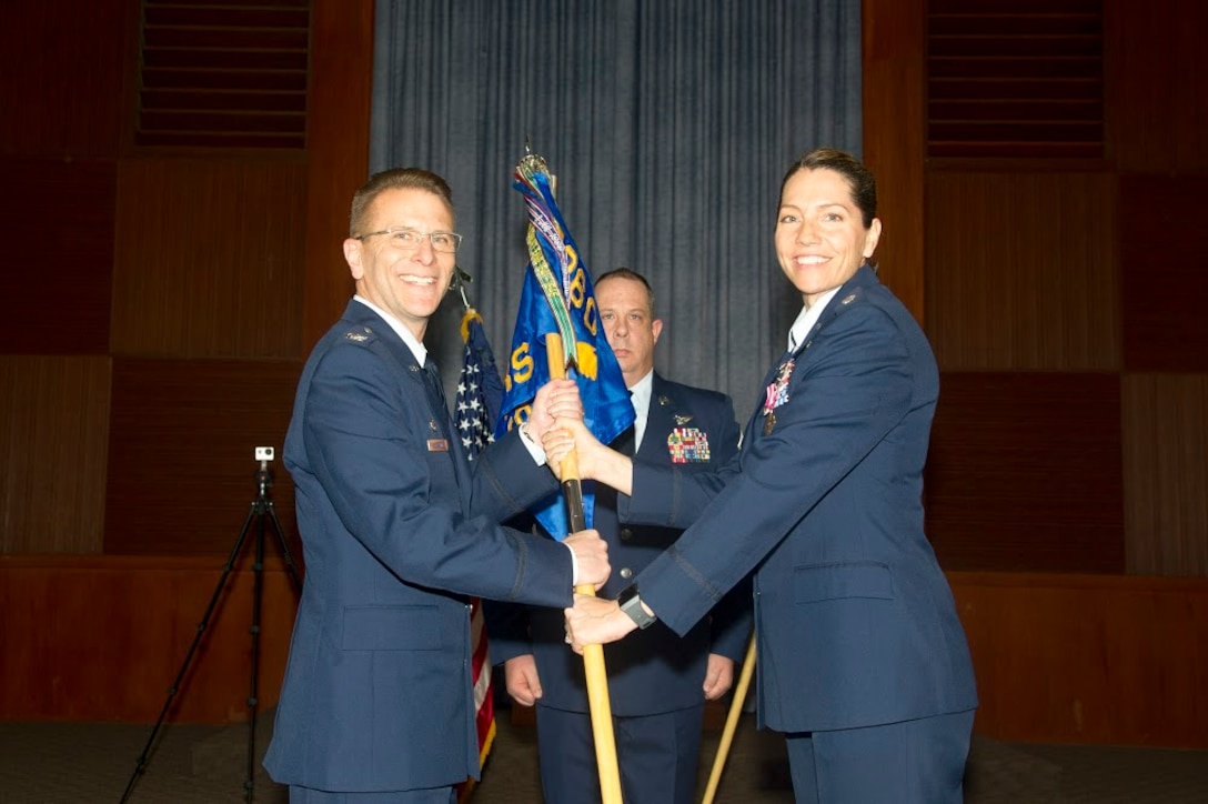 Lt. Col. Karyn L. Christen passes the 13th Reconnaissance Squadron guidon to Col. David S. Edwards, 726th Operations Group commander at Creech Air Force Base, Nevada, as she relinquishes command April 7 at Beale AFB, California.