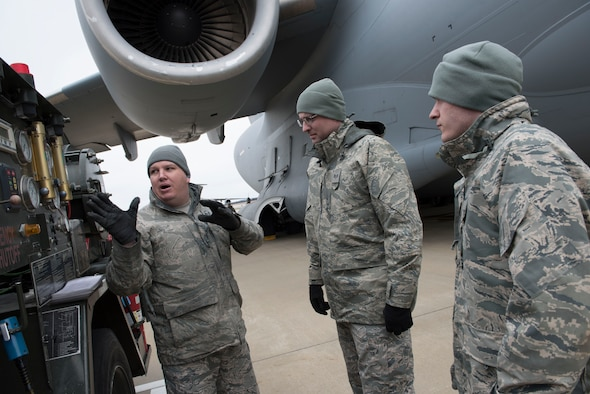 Master Sgt. Raymond Franze, left, a fuels management specialist for the 167th Airlift Wing, explains how to use a fueling truck at the Martinsburg, W.Va. air base, to Staff Sgt. Ryan Harmon and Airman 1st Class Richard Ahart, both fuels specialists for the 130th Airlift Wing, April 7. The 167th and the 130th Logistics Readiness Squadrons swapped ten Airmen over the April unit training assembly to afford them new training opportunities. (U.S. Air National Guard photo by Senior Master Sgt. Emily Beightol-Deyerle)