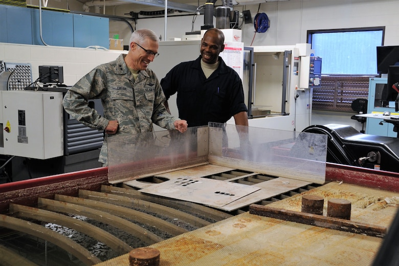 Master Sgt. Tony Shaw, the 302nd Maintenance Squadron metals technologies chief, explains how the squadron's water jet cutting center works to Maj. Gen. Craig La Fave, the 22nd Air Force commander, during his tour of the 302nd Airlift Wing's maintenance facilities at Peterson Air Force Base, Colorado, April 8, 2018. La Fave spent part of the morning learning about the squadron's challenges and accomplishments. (U.S. Air Force photo by Staff Sgt. Frank Casciotta)